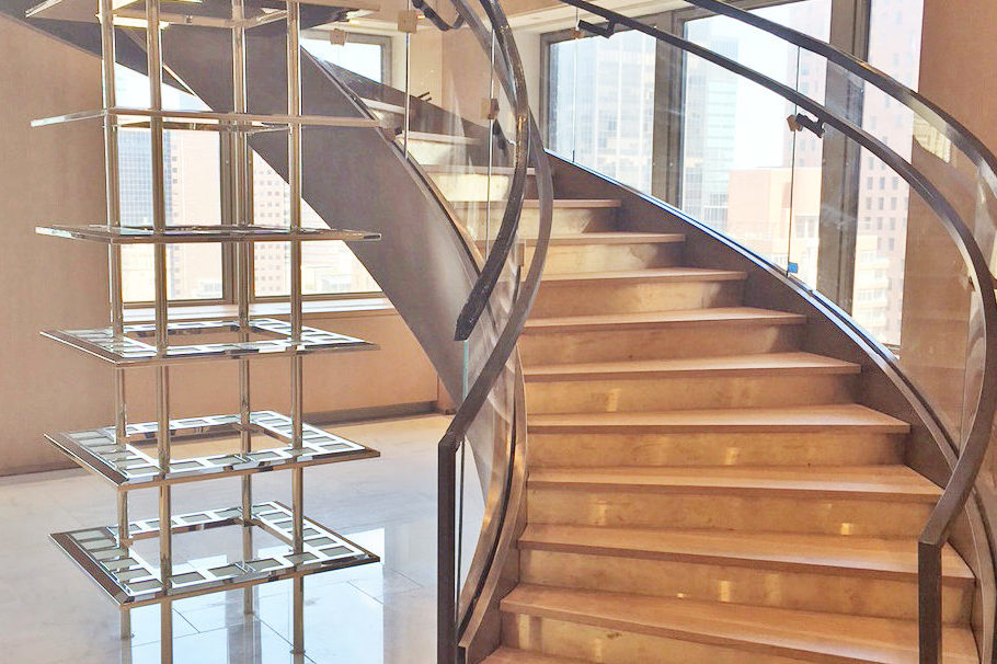 Custom Curved Bronze Clad Stringer + Glass Guardrail + Handrail.Angelo Gordon – 245 Park Avenue – New York, NYArchitect: Robert A.M. Stern Architects