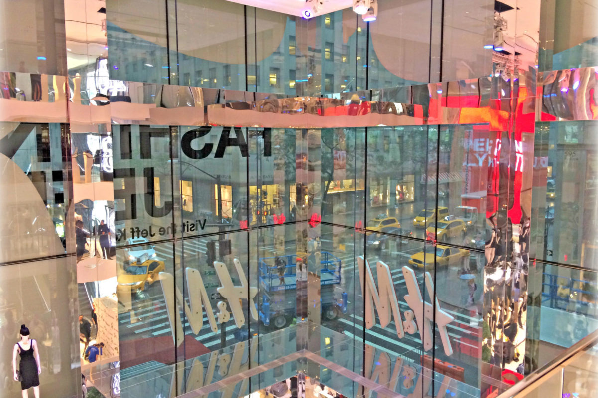 End Product A Seamless All Glass Storefront. Integrated Fittings Inside Of Glass For H&M Signage With Mirror Finish Clad Beams + Columns.